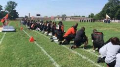 Members of Woodrow High School Tigers kneeling during the national anthem
